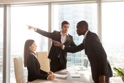Two employees standing and pointing while their boss is fired