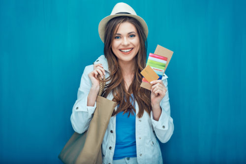Smiling woman holding passport and credit card