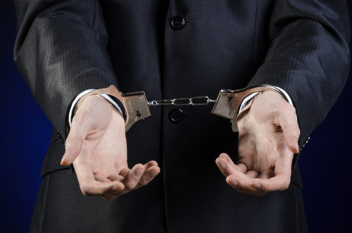 A close up of a man wearing a black suit, holding his hands out, palms up and open, with handcuffs around his wrists.