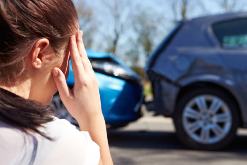 Woman holds head in front of car accident