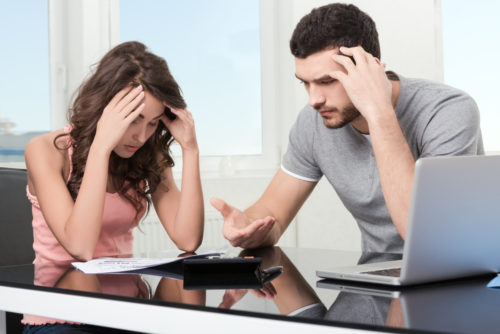 Man and woman upset looking at credit card statement.