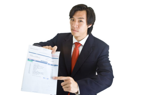 An Asian man points to a past due bill.