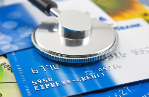 A stethoscope sits on top of a blue credit card.
