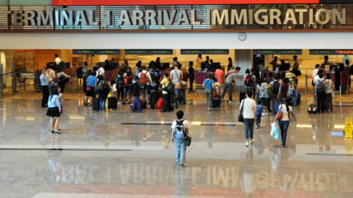 Immigrants arrive at the immigration terminal of an airport.
