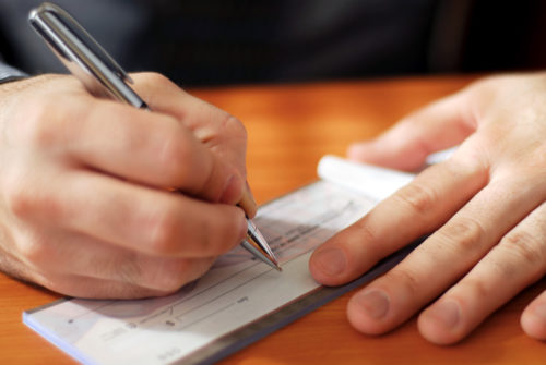 A close-up image of a man using a pen to fill out a check