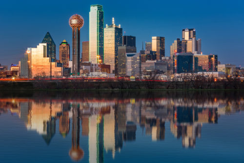 The Dallas skyline just after sunset, with the skyline reflected in the Trinity River.