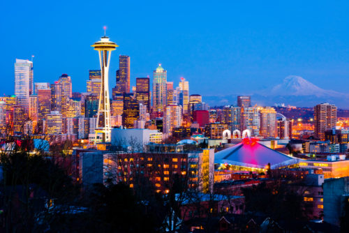 Panorama of downtown Seattle, Washington from a distance at night with buildings lighted up and Mount Rainier in background.