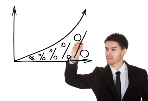 A man in a suit illustrates how interest grows exponentially over time by drawing a rising graph with percentage signs.