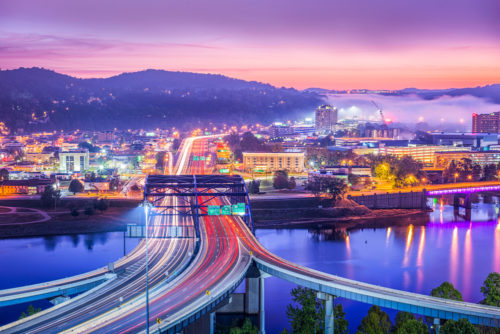 A sunset skyline view of Charleston, West Virginia, with mountains and rolling fog in the background. Long exposure.