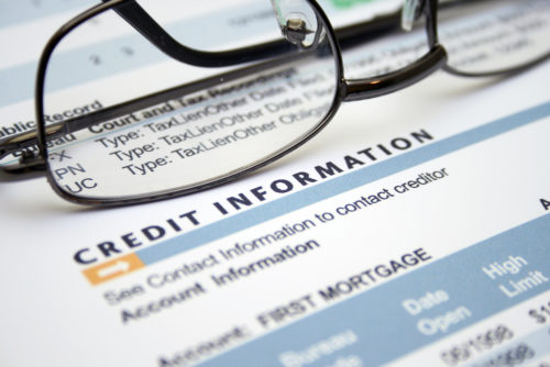 An image of eyeglasses sitting atop a credit information report.