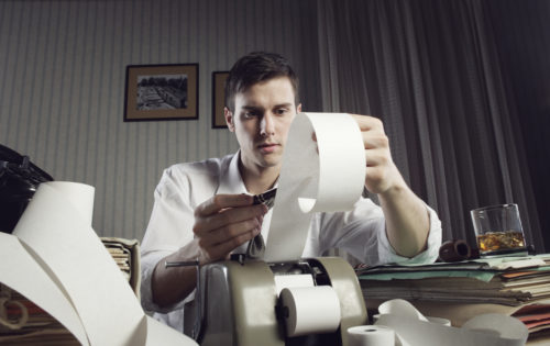 An image of a man holding up a receipt from a tax calculator