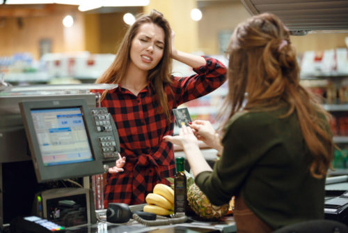 A woman in a plaid shirt looks confused as she tries to pay a woman at a grocery store cash register, who holds the first woman's debit card.
