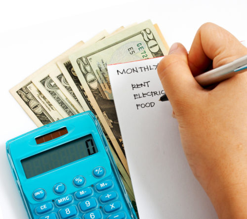 A hand writes out a budget on top of some money and next to a calculator.