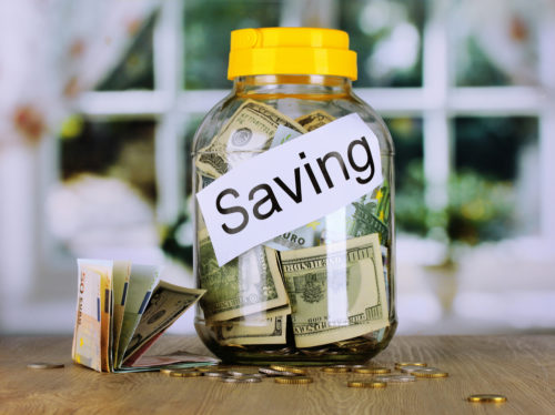"""A jar marked """"savings"""" with money in it sitting on a table."""