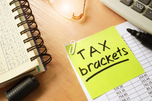 """A sticky note that reads """"tax brackets"""" is attached to a document of tax figures."""