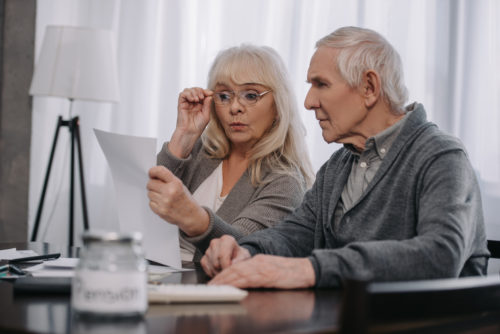 An elderly couple calculating taxes and credits for retirement.