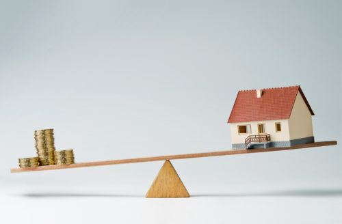 A model house and stacks of coins balancing against each other on a seesaw