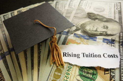 """Newspaper headline reading """"Rising Tuition"""" lying atop a pile of money, next to a graduation cap"""
