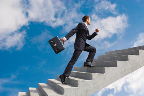 A businessman with a briefcase climbing up a ladder to the sky, signifying career development and growth.