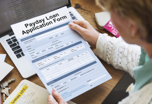 A woman holding a payday loan application form.