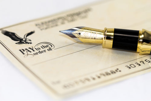 A fountain pen sits on top of a personal check.