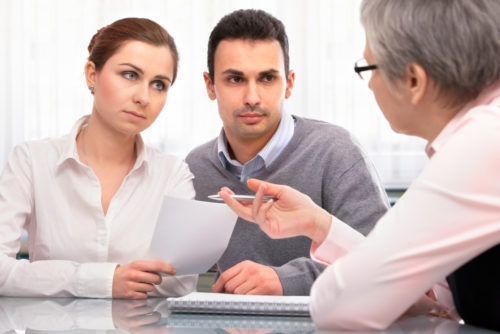 A man and woman talk to a financial planning consultant about cosigning.
