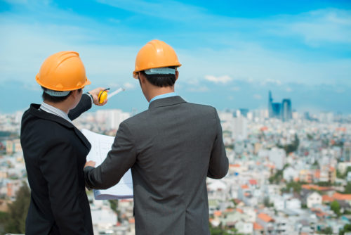 Two civil engineers in hardhats overlook a city while one holds plans in his hands.
