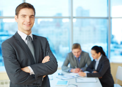 A young businessman looks at the camera smiling with his arms crossed while his coworkers talk in the background.