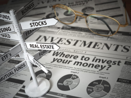 """Eyeglasses sit on top of a newspaper that reads """"Where to invest your money?"""" While a graphic of a direction sign has pointers on it with diverse investment options including """"Business,"""" """"Real Estate,"""" """"Mutual Funds,"""" """"Bonds,"""" and more."""