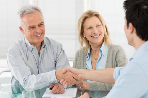 An elderly couple shaking hands with their financial advisor.