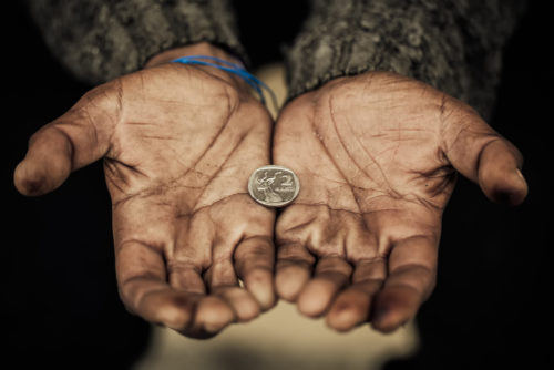 A poor man holds his hands out with one coin in it.