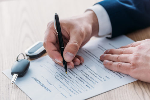 Keys sit on top of a car loan document that is being signed by a man.