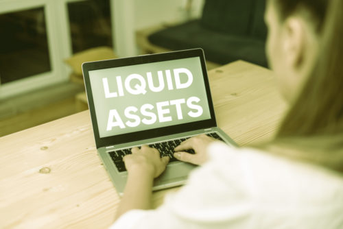 """A woman types on a laptop with a screen that reads """"liquid assets."""""""