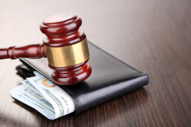 A gavel sits on top of a wallet where money can be seen through the top of it, symbolizing wage stagnation.