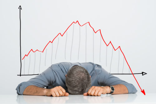 A small business owner lays his head on a table as a graph behind him depicts the financial crisis plunge.