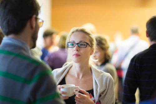 A businesswoman listening to a person at a networking event while drinking coffee.