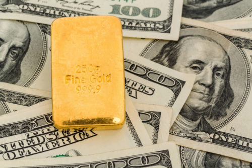 A gold bar sits on top of $100 bills.