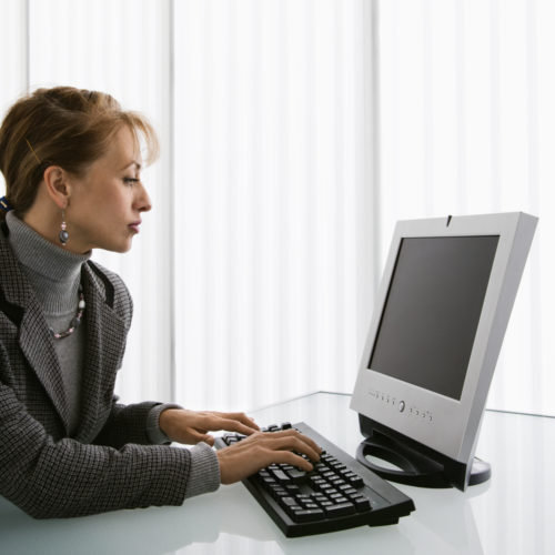 An administrative assistant working on a computer.