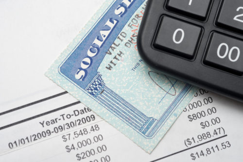 A Social Security card sits on top of tax figures and under a calculator.