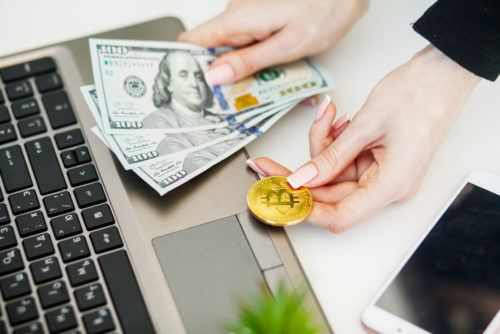 A woman sitting next to her laptop on a desk, holding cash in one hand and a bitcoin in the other.