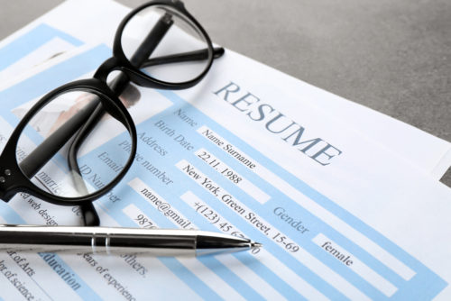 A pen and a pair of glasses sit on top of a resume.