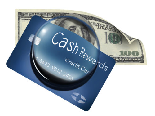 """A magnified dome clarifies the words """"cash rewards"""" on a credit card that sits on top of a $100 bill."""