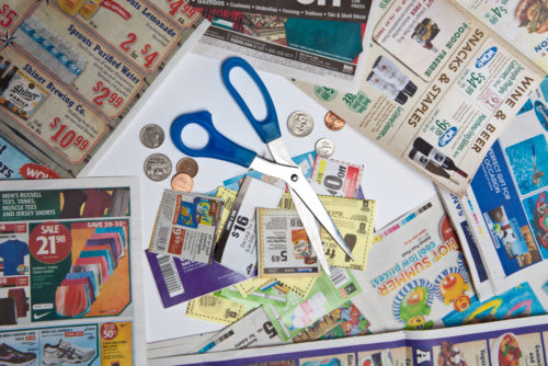 A pair of scissors and coins sit on top of coupons.
