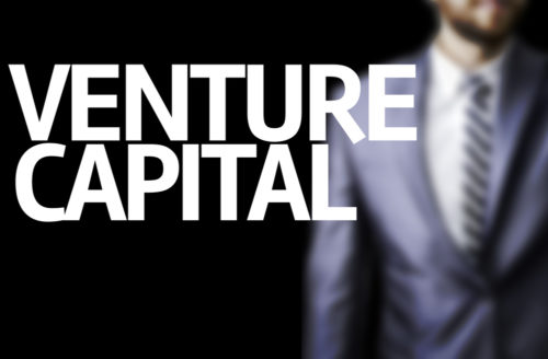 "An investor stands behind the words ""venture capital."""