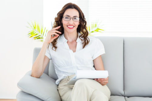 A smiling psychiatrist sitting on her couch, holding a notebook.