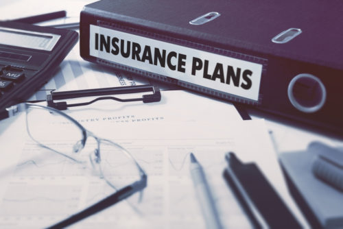 """A notebook labeled """"insurance plans"""" sits next to other loose documents, pens, eyeglasses, and a calculator."""