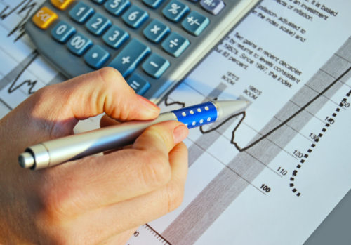 A hand holding a pen points to investment documents on a desk next to a calculator.