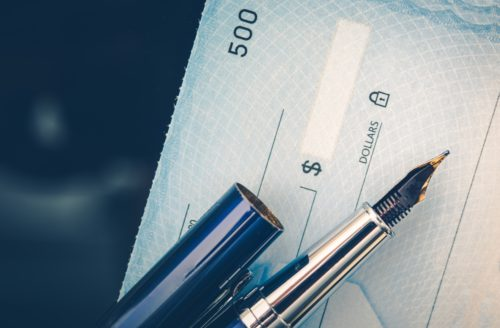 A fountain pen sitting on top of a check.