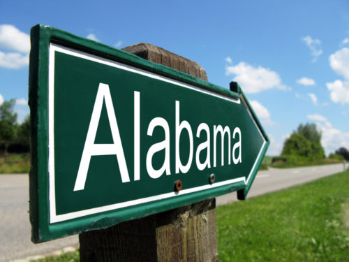 """A green sign in the shape of an arrow reads """"Alabama."""""""