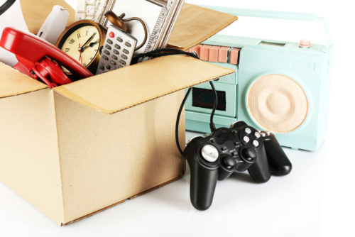 A box is filled with miscellaneous things that are ready to be sold, including a gaming controller, a clock, a radio, and more.